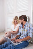 Young couple sitting on floor using laptop Royalty Free Stock Images