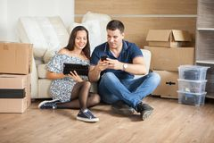 Young beautiful couple sitting on floor in their new flat royalty free stock image