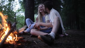Young couple sitting in a forest fire. The guy kisses the girl stock video