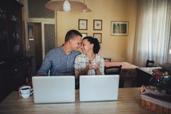 Young couple sitting in front of computers royalty free stock images