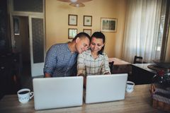 Attractive couple using laptop together on sofa to shop online a stock photography