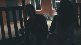 Young couple sitting on the front porch and talking stock video footage