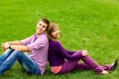 Young couple sitting on grass Royalty Free Stock Images