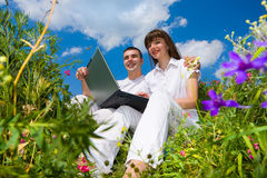 Young couple sitting on grass field with laptop Royalty Free Stock Images