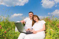 Young couple sitting on grass field with laptop Stock Photos