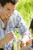 Young couple sitting on grass, focus on man holding camping mug, smiling, close-up Stock Photo