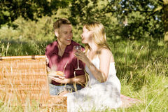 A young couple sitting on the grass, having a picnic Stock Images