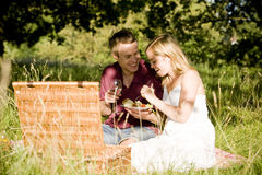 A young couple sitting on the grass, having a picnic Stock Photography