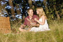 A young couple sitting on the grass, having a picnic Stock Photos