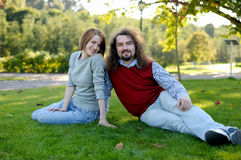 Young couple sitting on the grass in a park Stock Photos