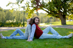 Young couple sitting on the grass in a park. Young couple is sitting on the grass in a park Royalty Free Stock Photo