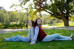 Young couple sitting on the grass in a park Royalty Free Stock Image
