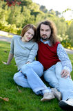 Young couple sitting on the grass in a park Stock Photo