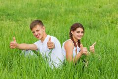 Young couple sitting on a green meadow royalty free stock images