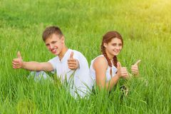 Young couple sitting on a green meadow royalty free stock photos