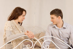 Young couple sitting having a private discussion Stock Images