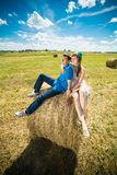 Young couple sitting on a hay stack Royalty Free Stock Photography