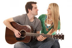 Young couple sitting holding hands looking at each other playing Stock Image