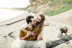 A young couple is smiling and hugging on the beach. Beautiful girl embrace her boyfriend from back. Wedding walk Stock Photo