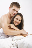 Young Couple Sitting In Bed Stock Image