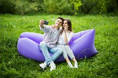 Young couple sitting on inflatable sofa lamzac and take selfie on phone while resting on grass in park stock images