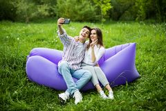Young couple sitting on inflatable sofa lamzac and take selfie on phone while resting on grass in park royalty free stock photography
