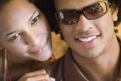 Young couple sitting inside tent, cheek to cheek, man wearing sunglasses, smiling, close-up, portrait Stock Photo