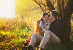 Young couple sitting and kissing near the tree Royalty Free Stock Photography