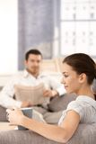 Young couple sitting in living room at home stock images