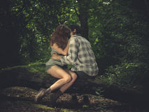 Young couple sitting on log and kissing Royalty Free Stock Images
