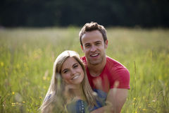 A young couple sitting in long grass embracing Royalty Free Stock Photo