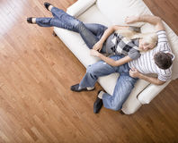 Young Couple Sitting on Love Seat. Young woman affectionately lays against a young man on a cream colored love seat. Horizontal shot Royalty Free Stock Image