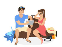 Young couple sitting on the luggage and using tablet pc to watch photos from their holiday Stock Images