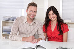 Young couple sitting in a meeting - holding hands. Stock Photo