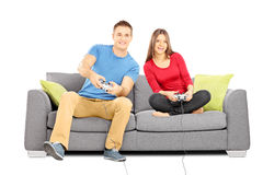 Young couple sitting on a modern couch and playing video games Stock Photos