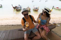 Young Couple Sitting Near Beach Eating Street Food And Drinking Fresh Juice, Happy Smiling Man And Woman Tourists Royalty Free Stock Photography