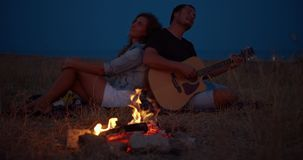 Young couple sitting near bonfire, man playing guitar. Romantic music and happy couple relationships. Romance couple stock video footage