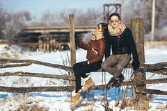 Young couple sitting on old fence Stock Image