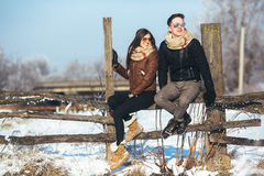 Young couple sitting on old fence Stock Photo