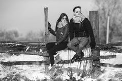 Young couple sitting on old fence Royalty Free Stock Image