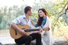 Free Young Couple Sitting On A Log By The River And Playing Guitar, Summer Nature, Bright Sunlight, Shadows And Green Leaves, Romantic Royalty Free Stock Images - 125271019