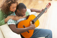 Young Couple Sitting On Sofa Playing Guitar Stock Images