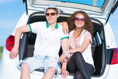 Young couple sitting in the open trunk Royalty Free Stock Image