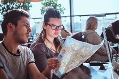 A young couple sitting in an outdoor caf planning to itinerary their journey. Portrait of a young couple sitting in an outdoor caf planning to itinerary their royalty free stock photography