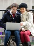 Young couple sitting outdoors looking at laptop together Royalty Free Stock Images