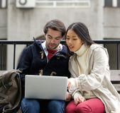 Young couple sitting outside on bench looking at laptop screen Royalty Free Stock Photo