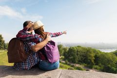 A young couple is sitting on a parapet. They embrace and the girl shows her hand somewhere in the distance. They have backpacks for traveling. Before them a Royalty Free Stock Image