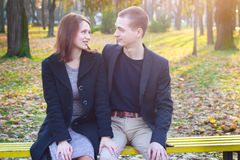 Young couple sitting on a park bench on a sunny autumn day and expressing tenderness Stock Photos