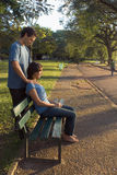 Young Couple sitting on a Park Bench - Vertical Stock Photo