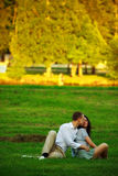 Young couple sitting on park lawn Stock Image
